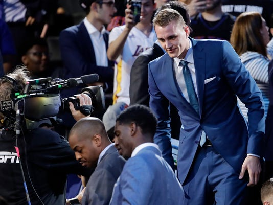 Anzejs Pasecniks steps down out of the arena seats after being selected by the Orlando Magic as the 25th pick overall during the NBA basketball draft, Thursday, June 22, 2017, in New York. (AP Photo/Frank Franklin II)