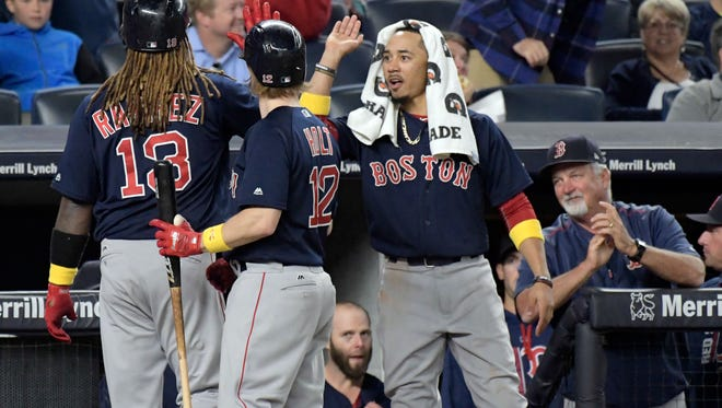 Red Sox batter Hanley Ramirez celebrates with Brock Holt and Mookie Betts, right, after hitting a home run.