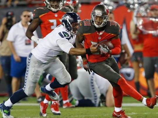 FILE -- Seattle Seahawks quarterback Russell Wilson (3) tackles Tampa Bay Buccaneers free safety Bradley McDougald (30) during the second half of an NFL football game at Raymond James Stadium. The Buccaneers won 14-5.