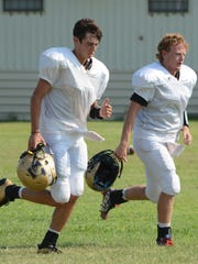 Abilene High quarterbacks Andrew Ezzell, right, and Kallin Sipe jog back to the field after a water break during practice Tuesday at the Eagles' on-campus practice field.