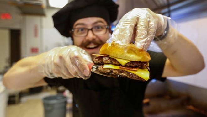 Omer Onder, owner of the Springfield Diner, takes a bacon double cheese burger off the grill.