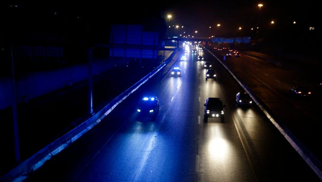 Blue lights illuminate a lane of Interstate 240 in Memphis near Jefferson as police cars participate in a Sea of Blue on Tuesday night for TBI Special Agent De'Greaun Frazier.