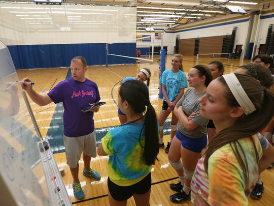 Shawn Strege, Webster Schroeder varsity volleyball coach, goes over the numbers from his squad's most recent match during practice at Schroeder High School Tuesday, Sept. 15, 2015.
