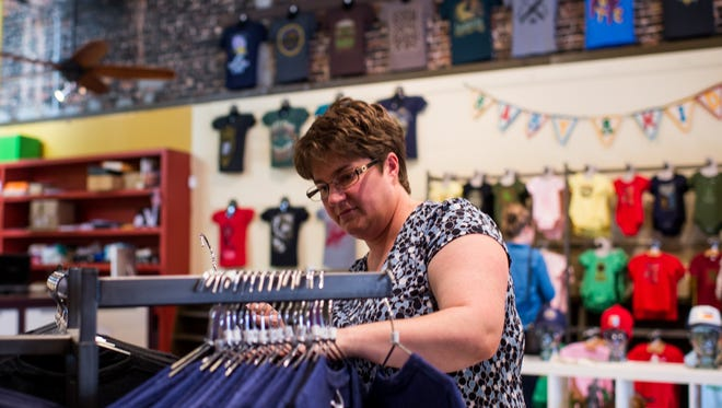 Renee Nunez looks through a rack of t-shirts at Parish Ink in Lafayette, La., during Small Business Saturday on Saturday, Nov. 28, 2015.