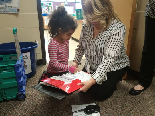 Kindergartner Amelia Green-Erving walks Kirkwood principal
