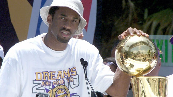 LOS ANGELES, UNITED STATES:  Kobe Bryant puts his hand on the NBA championship trophy at the end of the Los Angeles Lakers victory parade through downtown  Los Angeles 21 June 2000.  About 200,000 fans lined the streets to cheer on the Lakers  NBA 2000 championship.  (ELECTRONIC IMAGE)  AFP PHOTO/VINCE BUCCI (Photo credit should read Vince Bucci/AFP/Getty Images)