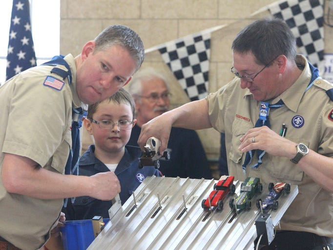 Andrew Kryger, left, Scott McCloud, 8, and Jeff McCloud set the cars in the starting gate for a race March 22, 2014. Stony Point Cub Scout Pack 17 held their annual Pinewood Derby at Kirkbride Hall in Stony Point.