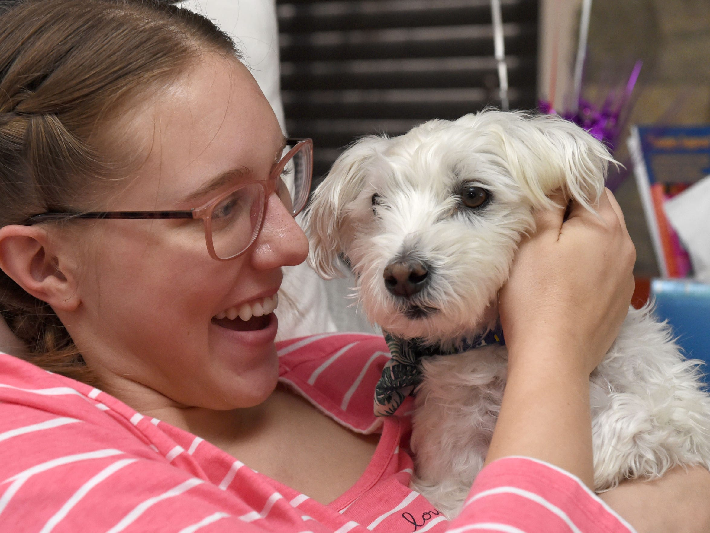 """Annika Kerns plays with her dog """"Buster"""" while on her"""