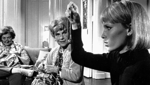 Rosemary (Mia Farrow, right) is visited by a couple