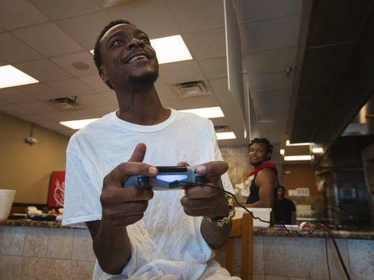 Former NFL player and Michigan State University star receiver Charles Rogers plays a video game at Basil's Pizza and Subs in Fort Myers Wednesday March 29, 2017. Rogers currently works at Uptown Motors.