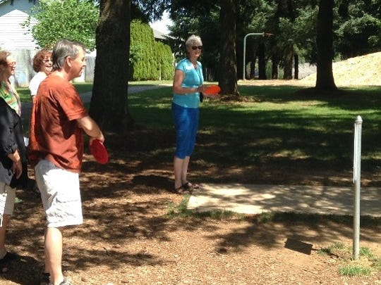 """Stayton Sublimity Chamber Director Kelly Schreiber gives the disc a whirl at Sublimity's Church Park disc-golf course Tuesday, June 7, during the third and final """"Canyon Tourism"""" group tour with GROW EDC, Travel Salem and Travel Oregon."""