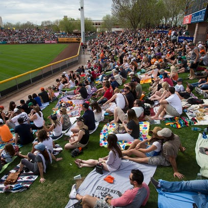 Fans fill the outfield lawn at Scottsdale Stadium.