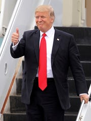 President Donald Trump gestures as he walks down the