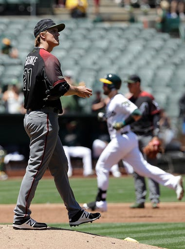 Arizona Diamondbacks pitcher Zack Greinke, left, reacts after allowing a home run to Oakland Athletics' Jonathan Lucroy, rear, during the third inning of a baseball game in Oakland, Calif., Sunday, May 27, 2018. (AP Photo/Jeff Chiu)