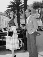 FILE - This June 26, 1953 file photo shows married actors Lauren Bacall, left, and Humphrey Bogart in Cannes during a  vacation on the French Riviera, France. Bacall, who died Tuesday, Aug.12, 2014, at 89, was a fashion darling of a unique sort. A model at 16, later a pal of Yves Saint Laurent and a frequent wearer of designs by Norman Norell.  (AP Photo, File)