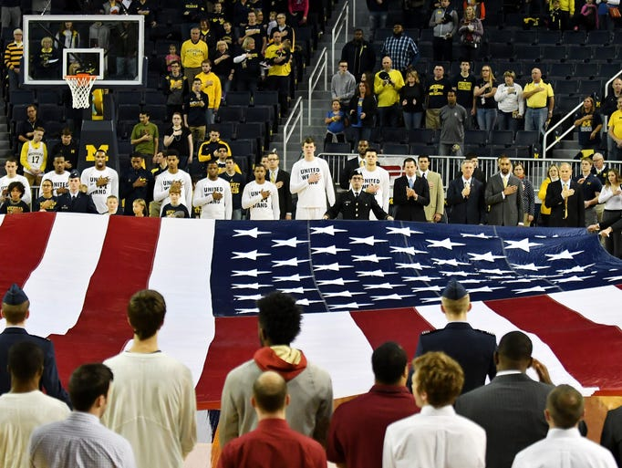 A large American flag is displayed on the court during