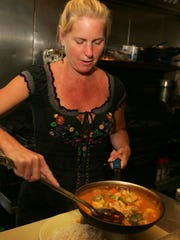 Tracie Orsi, owner of the Ragin' Cajun, prepares Chicken