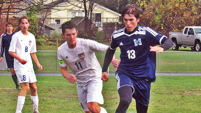 Mount Mansfield's Jacob Daigle (13) dribbles away from Mount Anthony's Franklin Cody (11) during Thursday's Division I boys soccer playdown in Bennington. MMU won 2-1 in OT.