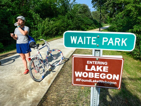 Sarah Weed stops for a drink of water after riding across the new bridge into Waite Park on the Lake Wobegon Trail extension Thursday, July 12, on a ride from the St. Joseph Trailhead.