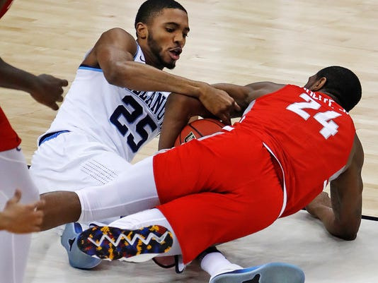 Villanova's Mikal Bridges (25) and Radford's Ed Polite Jr. (24) dive for a loose ball during the first half of an NCAA men's college basketball tournament first-round game in Pittsburgh, Thursday, March 15, 2018. (AP Photo/Gene J. Puskar)