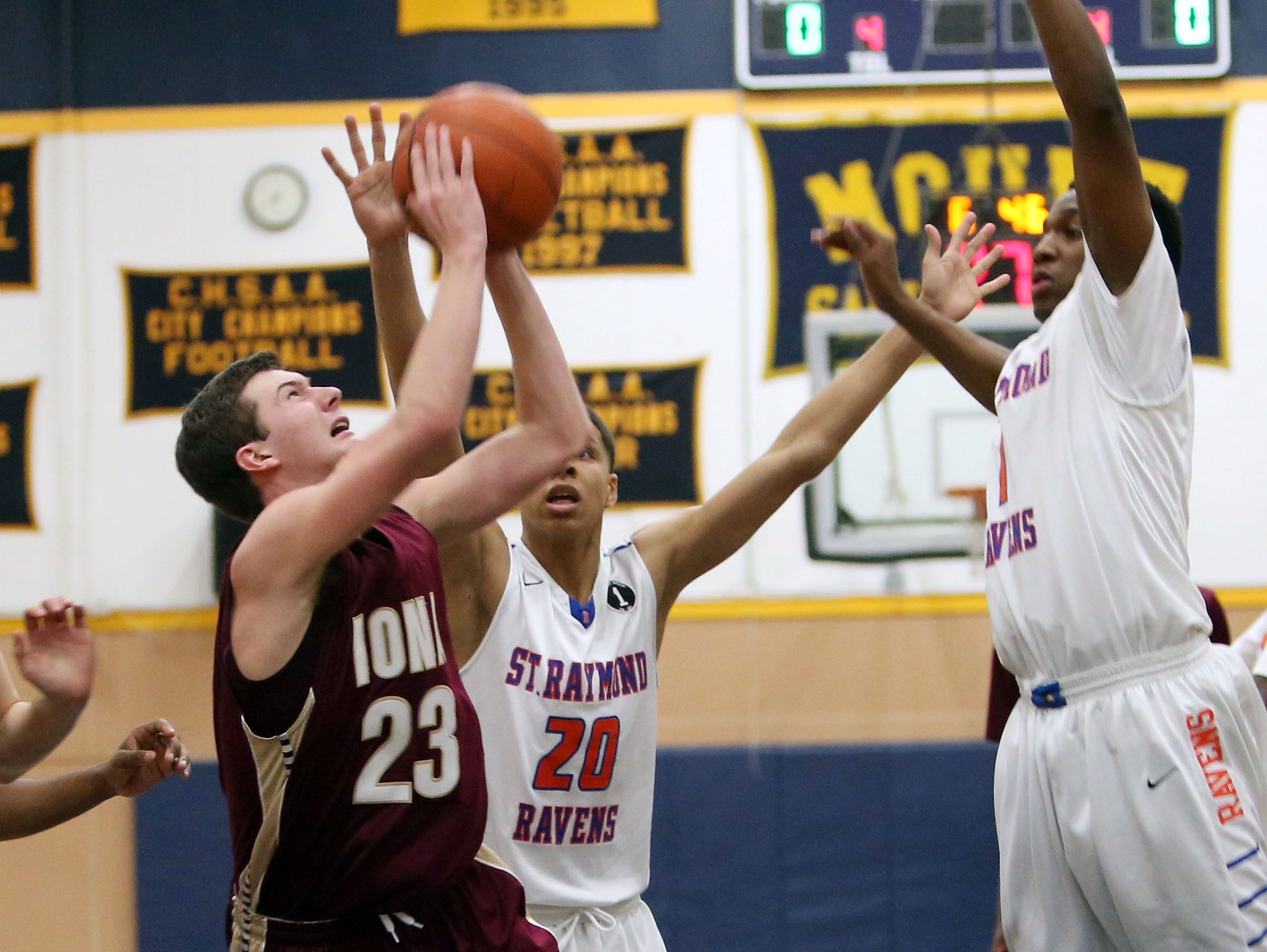 Iona's Patrick Fleming tries to get a shot off while being pressured by Saint Raymond's Joe Lupin (20) and Brain Adams (1) during the CHSAA Archdiocesan tournament semifinal at Mount Saint Michael Academy in the Bronx Feb. 23, 2016. Saint Raymond won the game 55-47.