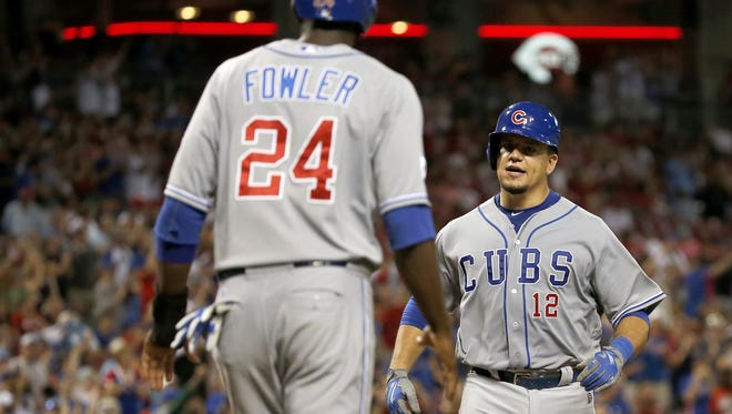 Middletown native and Chicago Cubs catcher Kyle Schwarber (12) is congratulated at home plate by center fielder Dexter Fowler after he hit a two-run, game-tying home run in the top of the ninth inning Tuesday night against the Reds at GABP.