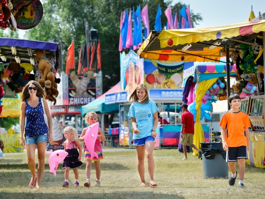 Courtney Backes (from left), her children Aubree and Macey, and family friends Katelyn Zimmer and Koye Zellner take in the sights of the Stearns County Fair in Sauk Centre, 2014.