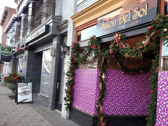Merchants obscure their store windows with wrapping paper before The Big Reveal.