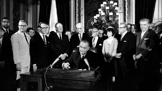 FILE - In this Aug. 6, 1965, photo, President Lyndon Baines Johnson signs the Voting Rights Act of 1965 in a ceremony in the President's Room near the Senate Chambers on Capitol Hill in Washington. Three years ago, the Supreme Court warned there could be constitutional problems with a landmark civil rights law that has opened voting booths to millions of African-Americans. Now, opponents of a key part of the Voting Rights Act are asking the high court to finish that provision off.  Surrounding the president from left directly above his right hand, Vice President Hubert Humphrey; House Speaker John McCormack; Rep. Emanuel Celler, D-N.Y.; first daughter Luci Johnson; and Sen. Everett Dirksen, R-Ill.  Behind Humphrey is House Majority Leader Carl Albert of Oklahoma; and behind Celler is Sen. Carl Hayden, D-Ariz.  (AP Photo)