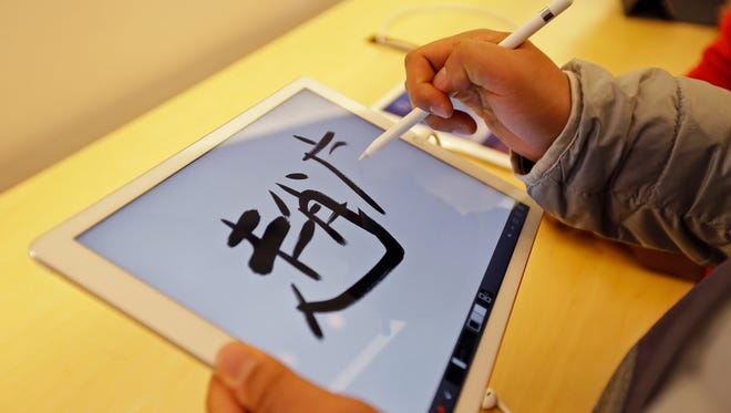 A man uses the Apple Pencil on the Apple iPad Pro at the Apple store Friday, Nov. 13, 2015, in San Francisco. The iPad Pro starts at $799, compared with $499 for the standard-size iPad Air 2 and $269 for the cheapest iPad, the 2-year-old iPad Mini 2. The newest iPad went on display in stores on Friday.