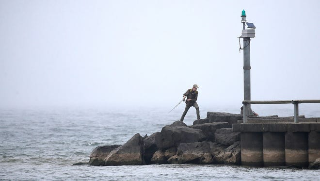 A lone fisherman maneuvers along the foggy pier in Webster Monday.