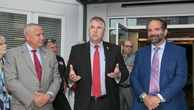 Somerville Mayor Brian Gallagher, flanked by state Sen. Kip Bateman (R-District 16), left, and Robert Weiss, owner of Weiss Properties, speaks at the grand opening celebration of the Cobalt Apartments on Veterans Memorial Drive.