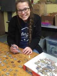 Allison Bristol paints one of over 300 puzzle pins