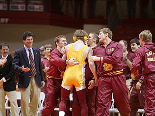 Mike Goebel, left, celebrates with his team after winning the 2007 IHSAA Wrestling Championships against Mishawaka.