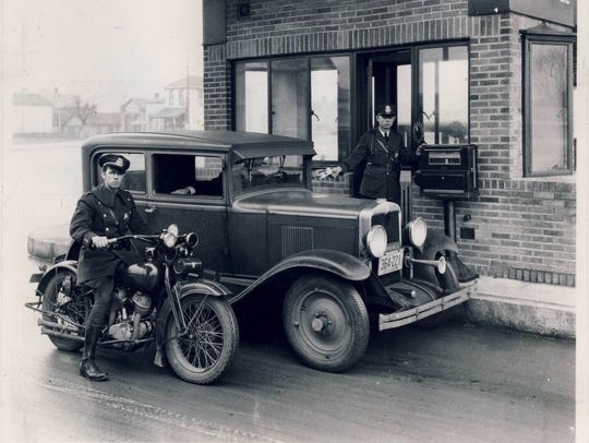 Toll enforcers flank a motorist paying at a toll house