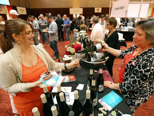 Sally Cruckshank, right, pours Seven from Airlie Winery for Jeni Felker, of Beaverton, during Chefs' Nite Out at the Salem Convention Center, Sunday, Oct. 4, 2015, in Salem, Ore. The event is a fundraiser for the Marion-Polk Food Share.