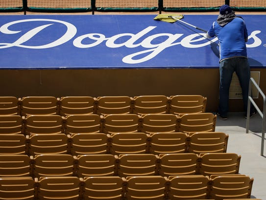 A worker cleans a sign before a spring training baseball