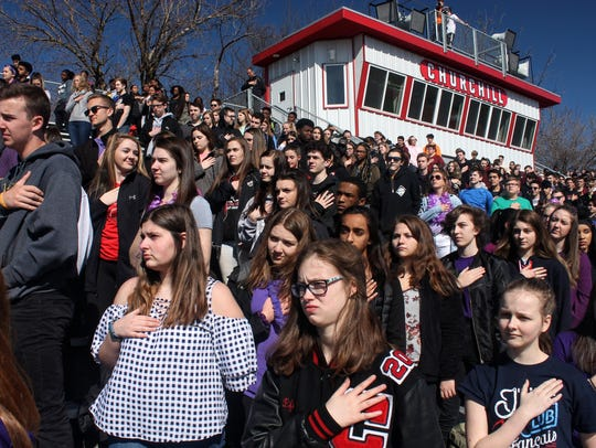 Students listen to the national anthem during the walkout