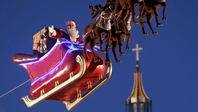 Santa Claus waves from a suspended sleigh over a Christmas market with Berlin's Dom cathedral in the background.