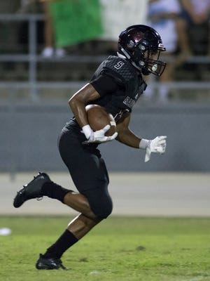 Dante Wright (5) runs during the Catholic vs Navarre high school football game in Navarre on Friday, August 25, 2017.