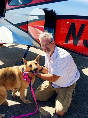 This June 6, 2016, photo provided by Best Fur Friends Rescue, shows Dr. Bill Kinsinger, with Jojo, a dog from Fort Worth Animal Care & Control, at a regional airport in northern Illinois. Officials said Thursday, Jan. 4, 2018, that Kinsinger, a doctor volunteering for a dog rescue operation who failed to land his small plane at an airport in Central Texas as planned and was later tracked by fighter jets flying over the Gulf of Mexico appeared unresponsive and may have been suffering from a lack of oxygen. A Federal Aviation Administration spokesman said the plane kept flying and was last observed on radar 219 miles northwest of Cancun, Mexico, flying at 15,000 feet. Kinsinger took off from Wiley Post Airport in Oklahoma City Wednesday afternoon after filing a flight plan to land in Georgetown, Texas. (Best Fur Friends Rescue via AP)
