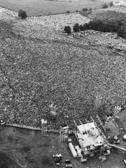 In this August 16, 1969 file aerial photo, music fans at the original Woodstock Music and Arts Festival are packed around the stage, at bottom, in Bethel.