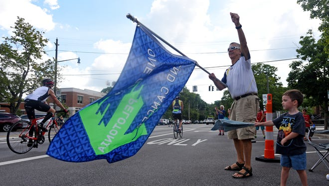 Newark resident Jeff Burns and his grandson Sloan Burns of Granville wave flags in support of Pelotonia riders Saturday morning in Granville.