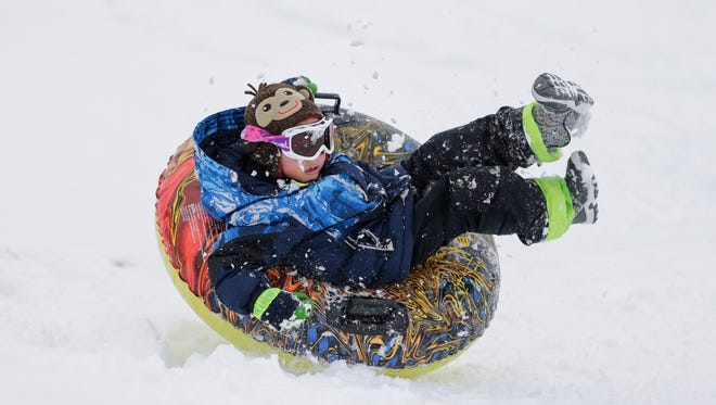 Victor Riebe, 6, takes a spill on his way down the sledding hill at Silver Creek Park Monday, Apr. 16, 2018, in Manitowoc, Wis.