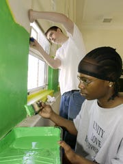 "Chris Crawford, front, and Dustin Robertson paint the interior of the Nelson Street Teen Center on Feb. 24, 2003. Greg Beam was in charge of the project, called ""Paint the Wallz,"" and transforming the space when he worked for Staunton Parks and Recreation as recreation programmer."