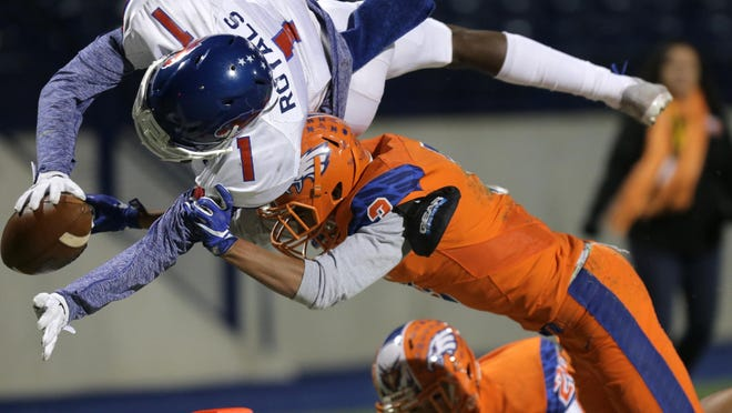 Abilene Cooper wide receiver Myller Royals dives into the endzone over Canutillo's Javier Arellano Friday in their area round game Friday at Grande Communications Stadium in Midland.
