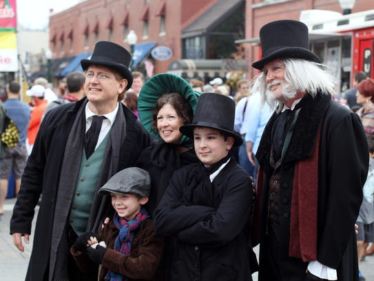 A Dickens family posing on Main Street at Dickens of