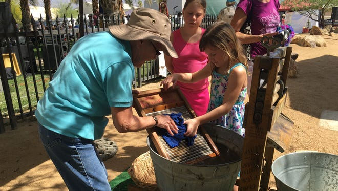 A volunteer with the Coachella Valley History Museum shows children how local pioneers did their laundry at the annual Heritage Festival on March 19, 2016.
