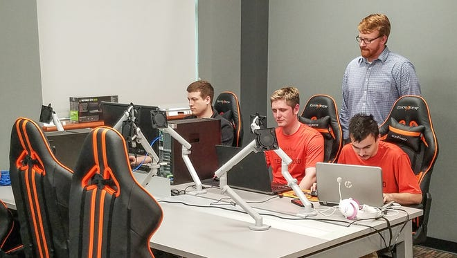 Indiana Tech eSports director Kyle Klinker observes (from left) Nathan Kirk, J.T. Carman and Kelly Hays during an eSports practice session.