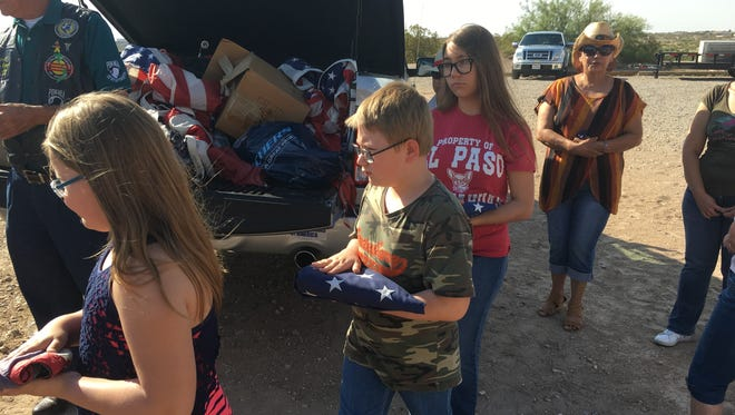Nataly Rose Durbin, 8, Nathaniel Anthony Durbin, 11, and Illiana Durbin, 13, take tattered flags to be inspected and burned at a flag retirement ceremony Saturday at American Legion Post 598 in Horizon City.